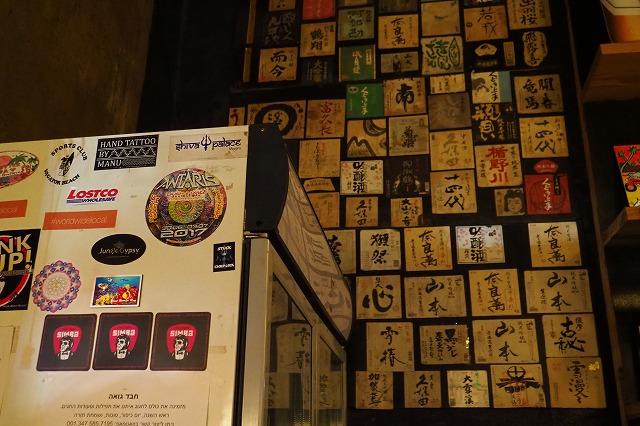 sakanaの壁の貼られた日本酒ラベルとantarisのステッカー